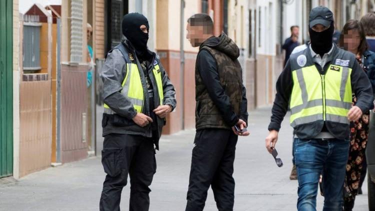 Dos agentes de la Policía Nacional caminan y hablan con algunas personas durante el registro de la casa en la que vivía el presunto yihadista. (EFE)