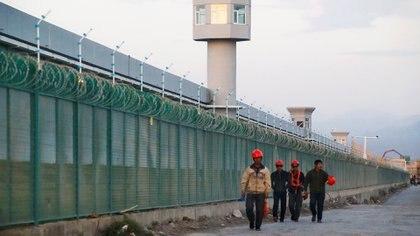 Los trabajadores caminan a lo largo de la cerca perimetral de lo que se conoce oficialmente como el centro de formación profesional en Dabancheng, en la Región Autónoma Uigur de Xinjiang, China (REUTERS / Thomas Peter / Foto de archivo)