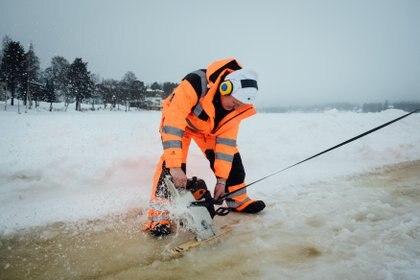 Un hombre usa una motosierra para cortar a lo largo del perímetro de un carrusel de hielo (Alessandro RAMPAZZO / AFP)