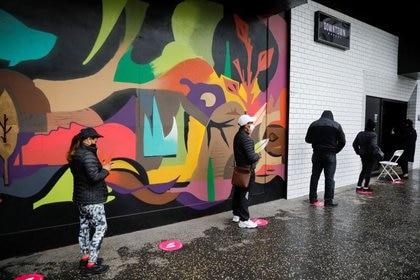 Clientes hacen una fila afuera de la discoteca LGBTQ+ Valetodo Downtown, que reabrió sus puertas como una tienda de alimentos mientras dure la restricción de cierre para clubes nocturnos debido a la pandemia del coronavirus (COVID-19), en Lima, Perú. 30 de junio de 2020. REUTERS/Sebastián Castañeda