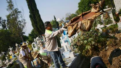A gravedigger throws rests of a coffin while he works to make space for new burials at the San Nicolas Tolentino cemetery, as the outbreak of the coronavirus disease (COVID-19) continues in Mexico City, Mexico May 24, 2020. REUTERS/Edgard Garrido     TPX IMAGES OF THE DAY