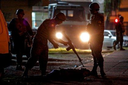 Un militar chileno apunta con su fusil a un civil que está en el suelo. (telam)