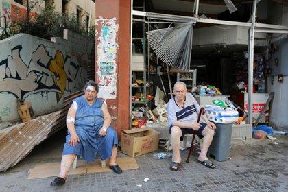 Una pareja que sufrió algunas heridas se sienta frente a su comercio, con daños materiales por la explosión (Reuters)