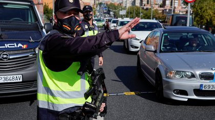 Spanish National Police officers wearing protective masks stand at a traffic checkpoint during a partial lockdown amid the outbreak of the coronavirus disease (COVID-19), in Madrid, Spain October, 9, 2020. REUTERS/Juan Medina