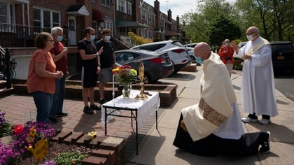 El reverendo Peter Purpura se arrodilla en un altar improvisado frente a una casa en el vecindario de Middle Village en Queens, el 17 de mayo de 2020 (James Estrin / The New York Times)