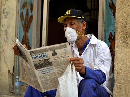 Un hombre lee un diario con una máscara en una calle de La Habana (Photo by Yamil LAGE / AFP)