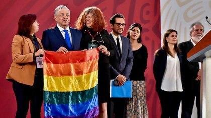 En el momento en que se despedía de quienes lo acompañaron en la conferencia matutina, los activistas se acercaron a Andrés Manuel López Obrador y él tomó la bandera gay y se colocó a un lado del atril Foto: Especial
