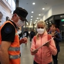 A woman shows papers to a police officer at a checkpoint in Constitucion railway station, as the spread of the coronavirus disease (COVID-19) continues, in Buenos Aires, Argentina April 1, 2020. REUTERS/Agustin Marcarian