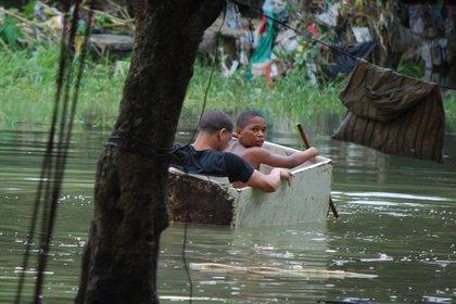 Dos niños flotan en el medio del agua a bordo de un improvisado bote (AP)