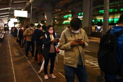 Personas con mascarillas hacen una fila en Taiwán. Foto: REUTERS/Ann Wang