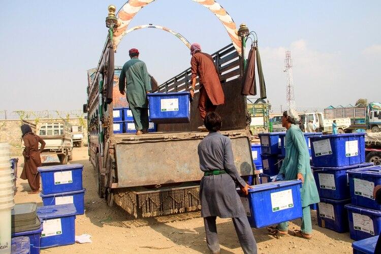 Empleados de la Comisión Electoral Independiente (IEC) cargan urnas en camiones en la provincia de Khost el 26 de septiembre (FARID ZAHIR / AFP)