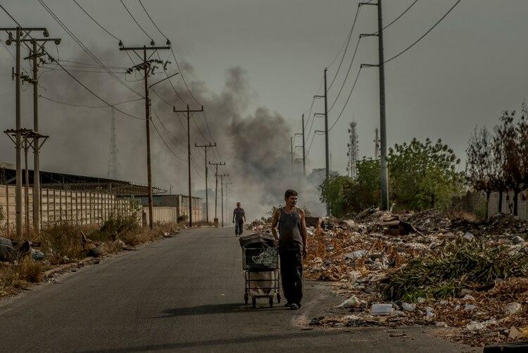 En Maracaibo, dos hombres revisan los desperdicios en busca de objetos que todavía sirvieran o que pudieran ser reciclados. (Meridith Kohut/The New York Times)