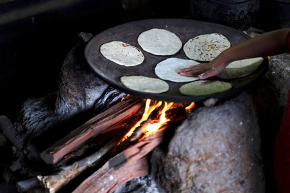 The daughter of Gonzalo Ramirez cooks tortillas at their home, in La Palmilla, Guatemala October 9, 2020. Picture taken October 9, 2020. REUTERS/Josue Decavele