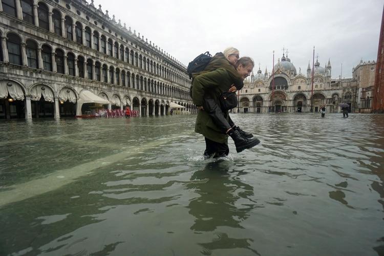 Un hombre lleva a una mujer a través de las aguas de la inundación en la Plaza de San Marcos (EFE/EPA/ANDREA MEROLA)
