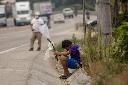 Un niño ondea una bandera blanca en la carretera pidiendo ayuda por hambre debido a la crisis economica provocada por el coronavirus, el 29 de abril de 2020 en El Tejar (Guatemala). EFE/Esteban Biba/Archivo