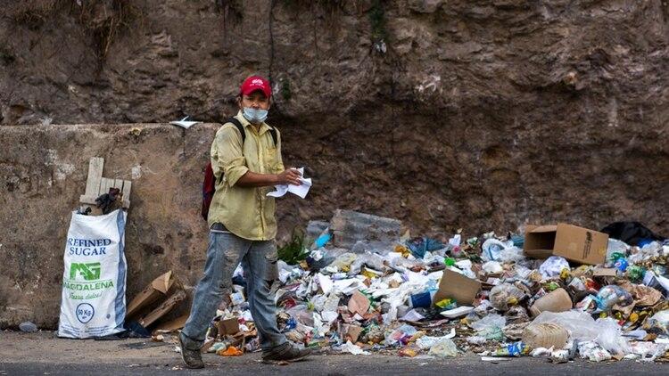 Un hombre se limpia las manos junto a un basural (AFP)