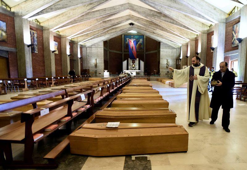 Un sacerdote local bendice los ataúdes almacenados en una iglesia debido al alto número de muertes, antes de que se los lleven los camiones del ejército, mientras Italia lucha por contener la propagación del coronavirus en Seriate, Italia, el 28 de marzo de 2020. REUTERS/Flavio Lo Scalzo