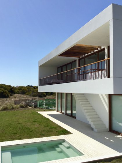 La vivienda de los arquitectos Lisandro De Sanctis y Josefina Belfiori se eleva del suelo para aprovechar la vista privilegiada a la cancha de golf y laguna
