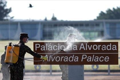 Miembros de las fuerzas armadas desinfectan la entrada del Palacio Alvorada, unas horas después de que el presidente diera positivo en su test de coronavirus. En las dos semanas previas, Bolsonaro mantuvo decenas de reuniones con sus ministros y colaboradores e hizo cuatro viajes al interior de Brasil. REUTERS/Ueslei Marcelino