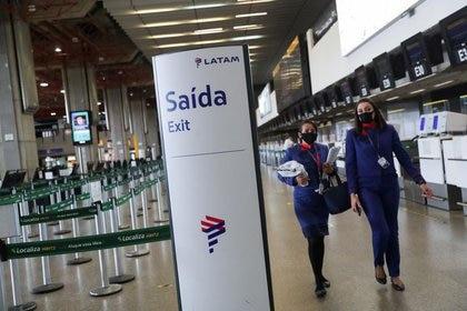 Dos empleadas de Latam Airlines caminan frente a unos mostradores de facturación en el Aeropuerto Internacional de São Paulo-Guarulhos en Guarulhos, cerca de São Paulo, Brasil, el 19 de mayo de 2020. REUTERS/Amanda Perobelli