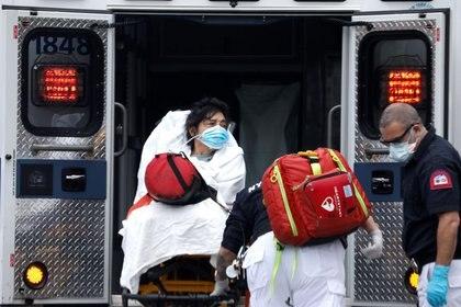 Una mujer es subida a una ambulancia por paramédicos en el vecindario de Harlem en Manhattan durante el brote de COVID-19, la enfermedad causada por el coronavirus, en la Ciudad de Nueva York, Nueva York (REUTERS/Mike Segar)