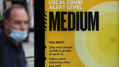 """A pedestrian wearing a face mask or covering due to the COVID-19 pandemic, walks past an electronic board displaying the Local Covid Alert Level as """"MEDIUM"""", on a bus-stop shelter in the West End of London on October 15, 2020. - Some nine million people in the British capital are facing more stringent coronavirus restrictions because of a rising number of cases, London Mayor Sadiq Khan said on Thursday. """"It is my expectation that the government will announce today that London will shortly be moving into tier two, or the high alert level of restrictions,"""" he told the London Assembly. (Photo by Daniel LEAL-OLIVAS / AFP)"""