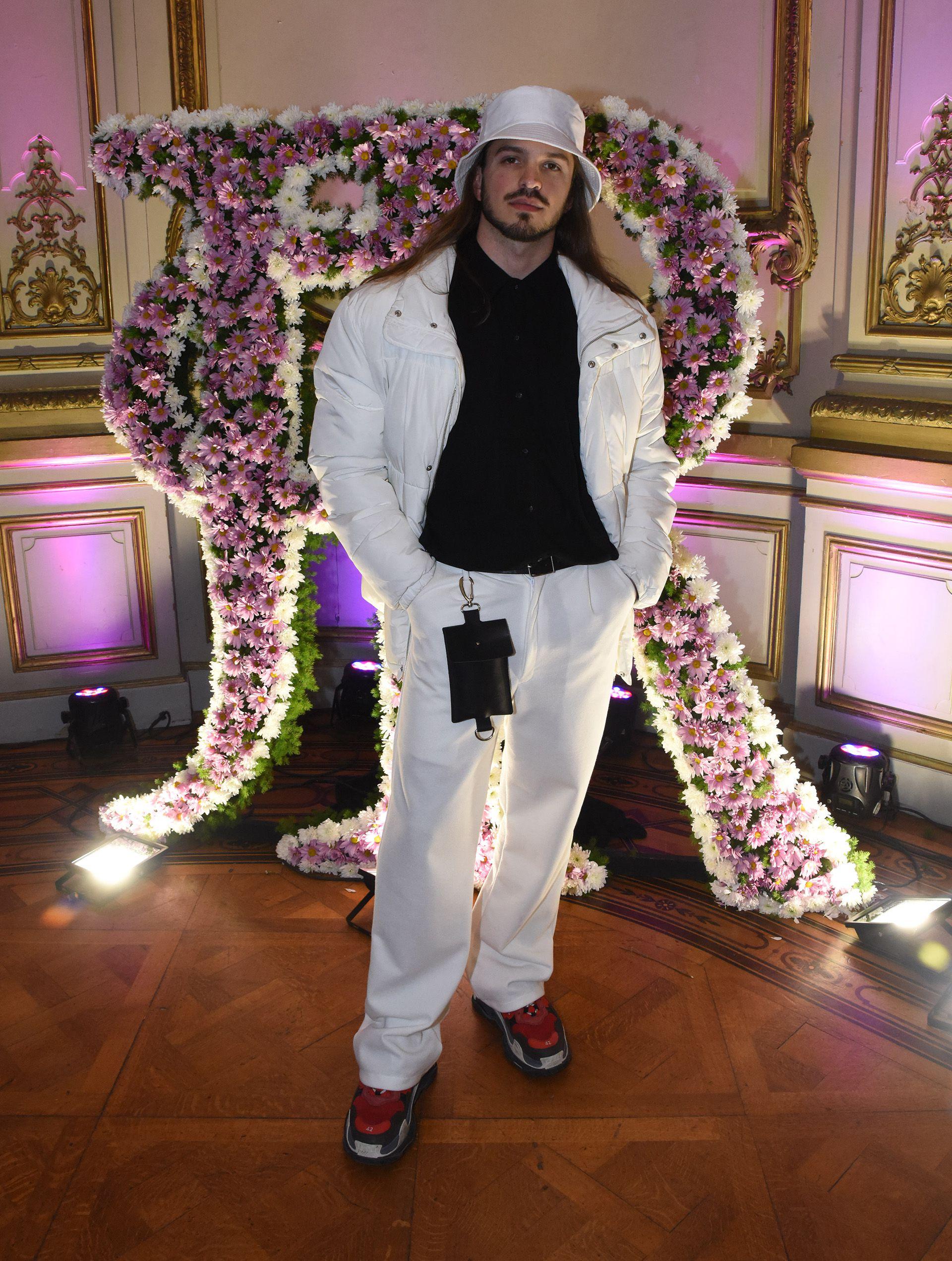 """El diseñador Juan Sartor, ex participante del concurso Corte y Confección lució un conjunto de pantalón blanco, camisa y campera """"puffer jacket"""" en blanca. Completó su look con el gorro tendencia, el gorro piluso"""