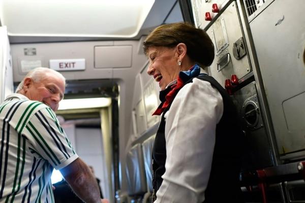 La azafata de American Airlines Bette Nash, de 81 años, saluda a los pasajeros al llegar al aeropuerto Ronald Reagan Washington en Arlington, Virginia, el 19 de diciembre de 2017 (AFP – Eric BARADAT )