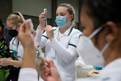 Personal sanitario fue registrado este sábado al preparar vacunas contra la covid-19, durante una jornada de vacunación masiva, en el Centro de Convenciones Walter E. Washington, en Washington DC (EE.UU.). EFE/Michael Reynolds
