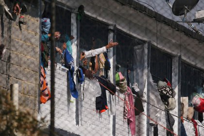 Reclusos sacan los brazos por las ventanas de sus celdas dentro de la prisión La Modelo después de un amotinamiento de reos que exigían al gobierno medidas sanitarias contra la propagación del (COVID-19), enfermedad provocada por el coronavirus, en Bogotá, REUTERS/Leonardo Munoz