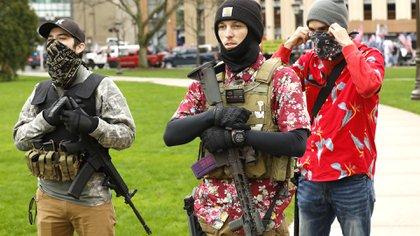 """En esta foto de archivo tomada el 30 de abril de 2020 manifestantes armados participan en un """"American Patriot Rally"""" en las escaleras del Capitolio del Estado de Michigan, exigiendo la reapertura de los negocios (Foto de JEFF KOWALSKY / AFP)"""