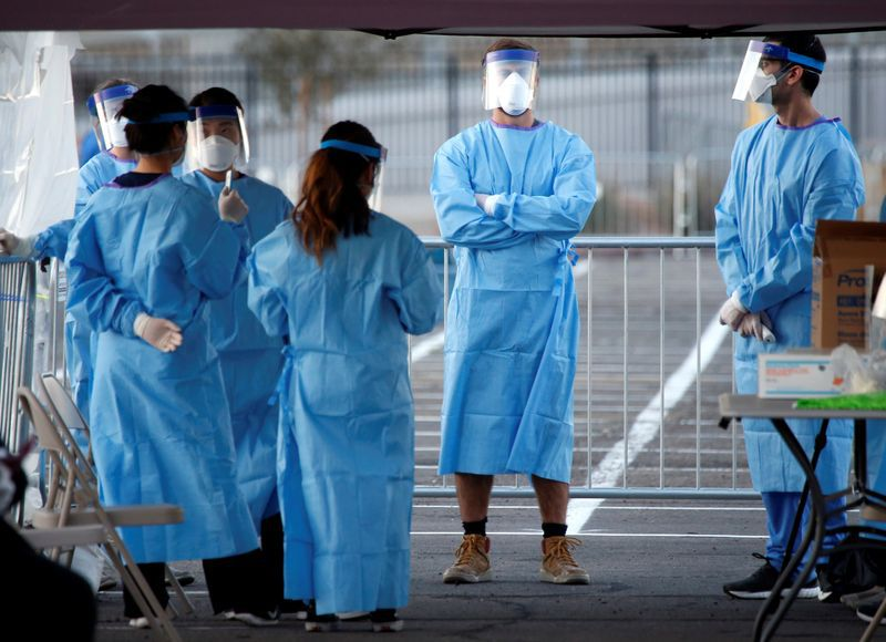Medical students and physician assistants from Touro University Nevada wait to screen people in a temporary parking lot shelter at Cashman Center, with spaces marked for social distancing to help slow the spread of coronavirus disease (COVID-19) in Las Vegas, Nevada, U.S. March 30, 2020. REUTERS/Steve Marcus
