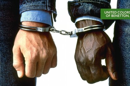 """1989.La campaña se llamó """"Campaña en blanco y negro"""", y el fin perseguido fue el de crear conciencia sobre el mundo y la igualdad de los derechos humanos, sin importar la raza. Dos personas con esposas. Un hombre blanco y uno negro. Esta imagen está incluida en una serie de fotografías que representaban hombres y mujeres de diferentes nacionalidades"""