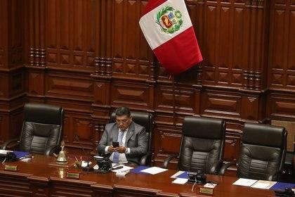 El congresista y primer vicepresidente del congreso, Mario Mantilla, utiliza su teléfono durante su participación en el pleno del Congreso en Lima. (EFE/Ernesto Arias)