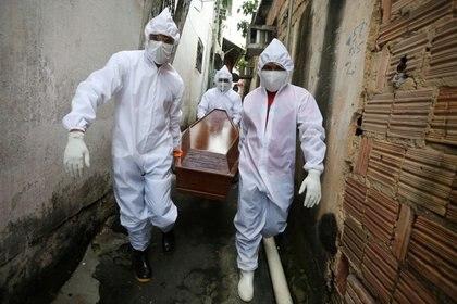 Trabajadores de Funeral SOS, con ropa protectora, llevan ataúd, barrio de Colonia Oliveira Machado en Manaos, Brasil.