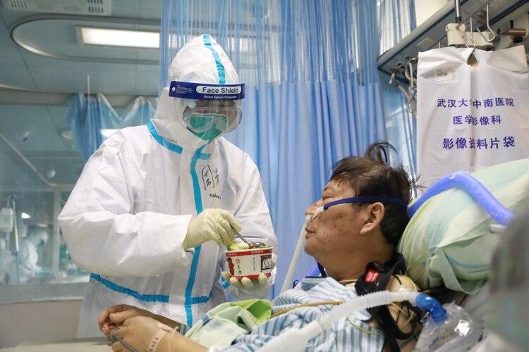 Una enfermera en traje protector alimenta a un paciente con coronavirus dentro de una sala aislada del Hospital Zhongnan de la Universidad de Wuhan (China Daily vía REUTERS)