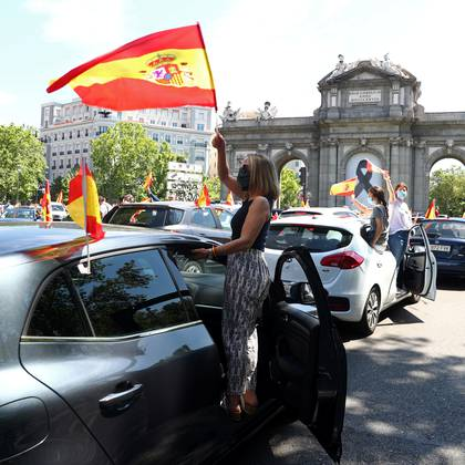 A demonstrator wearing a protective face mask waves a Spanish flag in front of Alcala Gate during a drive-in protest organised by Spain's far-right party Vox against the government's handling of the coronavirus disease (COVID-19) pandemic in Madrid, Spain, May 23, 2020. REUTERS/Sergio Perez