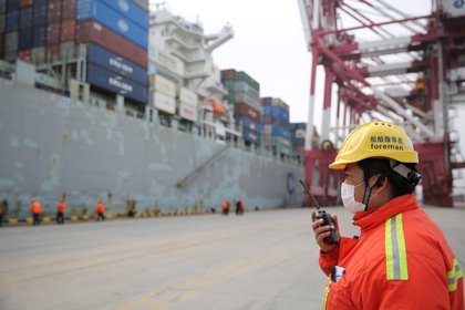 Un trabajador con barbijo cerca de un buque de carga en una terminal de contenedores del puerto de Qingdao en la provincia de Shandong, China, en una foto del 4 de febrero de 2020. (cnsphoto a través de REUTERS)