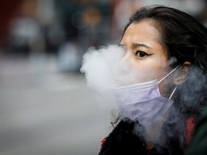 A woman exhales after vaping in Times Square, during the coronavirus disease (COVID-19) outbreak, in New York City, U.S., March 31, 2020. REUTERS/Brendan McDermid