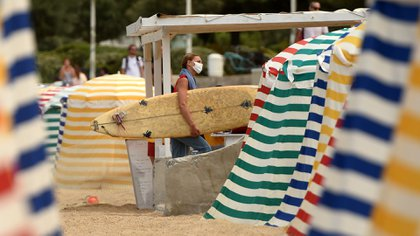 A surfer wearing a protective face mask walks on the beach, on August 3, 2020 in Biarritz, amid the crisis linked with the Covid-19 pandemic caused by the novel coronavirus. - Outdoor mask-wearing has also been made mandatory in parts of the northern region of Mayenne, as well as the popular coastal holiday destinations of Biarritz, Saint-Malo and Le Touquet. (Photo by GAIZKA IROZ / AFP)