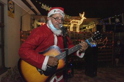Un cantante disfrazado de Santa, en su vivienda de Bothasig, un suburbio de Ciudad del Cabo (Photo by RODGER BOSCH / AFP)
