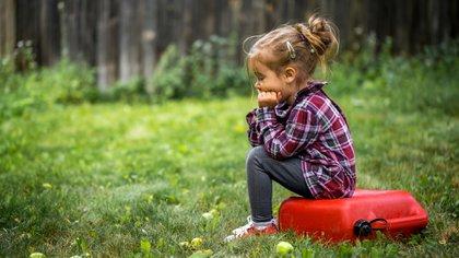 Niña triste sentada en un jardín