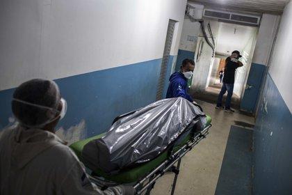 Profesionales de la salud cargan el cuerpo de una persona víctima de COVID-19 en el Hospital General de Manacapuru, el 8 de junio de 2020, en Manacapuru, Amazonas (Brasil). EFE/Raphael Alves