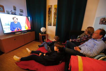 Una familia en Berlín observa el mensaje de la canciller Angela Merkel este 18 de marzo de 2020 (REUTERS/Fabrizio Bensch)