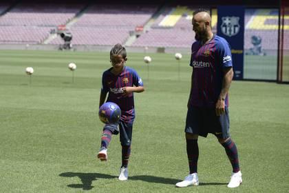 El día de la presentación oficial deArturo Vidalen Barcelonaobserva a su hijo Alonso también con la cresta que es característica en la figura chilena / AFP PHOTO / Josep LAGO