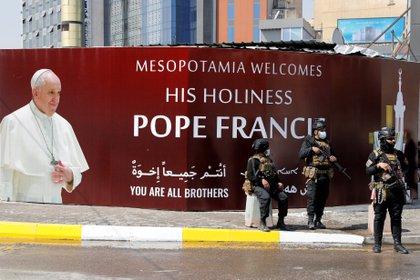 """Fuerzas de seguridad frente a una pancarta que dice: """"La Mesopotamia le da la bienvenida al Papa Francisco"""" en Baghdad (REUTERS/Khalid al-Mousily)"""
