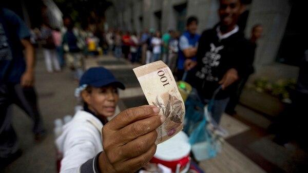 Los venezolanos hacen largas filas en los bancos paraconseguir billetes (AP)