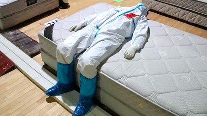 Jiang Wenyang recostado sobre una cama de uno de los hospitales temporales de China para tratar a pacientes con coronavirus