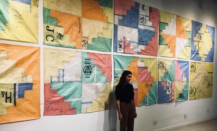 Candelaria Traverso, con su tapices de plástico de arpillera detrás