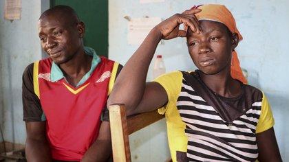 Danssanin Lanizou, de 30 años, a la derecha, se sienta con su marido, Yakouaran Boue, mientras su hija de un mes, Haboue Solange Boue, recibe tratamiento médico para la malnutrición grave en el centro de alimentación del principal hospital de la ciudad de Hounde, provincia de Tuy, en el suroeste de Burkina Faso (AP Photo/Sam Mednick)